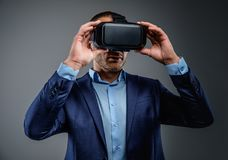 Male in a suit with virtual reality glasses on his head. Isolated on grey background Royalty Free Stock Images