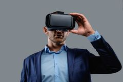 Male in a suit with virtual reality glasses on his head. Isolated on grey background Royalty Free Stock Image