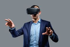 Male in a suit with virtual reality glasses on his head. Isolated on grey background Stock Photos