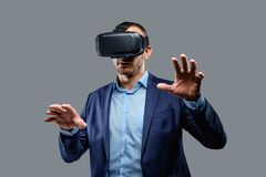 Male in a suit with virtual reality glasses on his head. Isolated on grey background Stock Photography