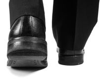 Male suit walking away in black shoes. Closeup of male suit walking away in black worn shoes towards white Stock Image