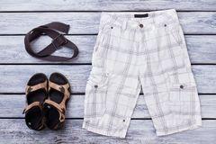 Male summer apparel, flat lay. White checkered male shorts, sandals and strap Stock Image