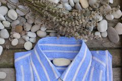 Male summer shirt on an wooden surface. Background. Male summer shirt,river pebbles and lavender twigs on a wooden surface Stock Images