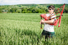 Male in sunglasses enjoying playing pipes in traditional kilt on green outdoors copy space summer field. Stock Photos