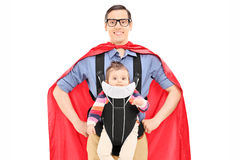 Male superhero carrying his baby daughter. Isolated on white background Stock Photos