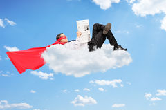 Male superhero lying on cloud and reading a newspaper Royalty Free Stock Images