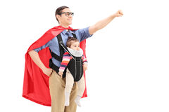 Male superhero with raised fist carrying a baby Royalty Free Stock Images