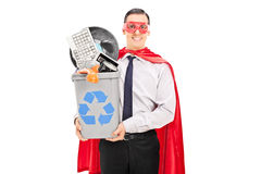 Male superhero recycling his old stuff. In a recycle bin isolated on white background Royalty Free Stock Image