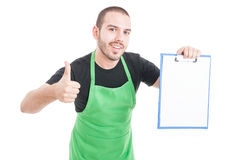 Male supermarket employee making thumb up gesture holding clipbo. Ard isolated on white background with advertising area Stock Images
