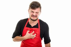 Male supermarket employer holding chest like in pain. Isolated on white background Royalty Free Stock Image