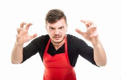 Male supermarket employer holding hands like scaring someone. Isolated on white background Stock Image