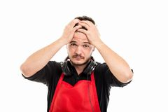 Male supermarket employer holding head wearing headphones. Like something happened isolated on white background Royalty Free Stock Photo