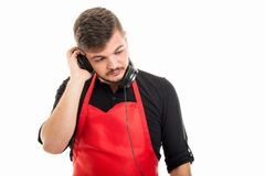 Male supermarket employer listening to one headphone. Like dj concept isolated on white background Royalty Free Stock Image
