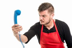 Male supermarket employer looking angry at blue phone receiver Royalty Free Stock Photos