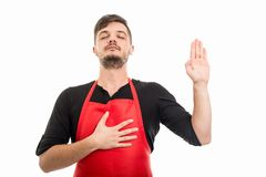 Male supermarket employer making oath gesture. With eyes closed isolated on white background Stock Photos