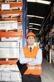 Male Supervisor With Arms Crossed At Warehouse. Confident young male supervisor in orange protective vest with arms crossed at warehouse Royalty Free Stock Photography
