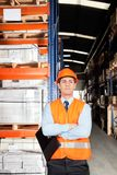 Male Supervisor With Arms Crossed At Warehouse. Confident young male supervisor in orange protective vest with arms crossed at warehouse Royalty Free Stock Photos