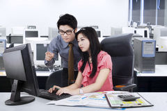 Male supervisor assist his employee. Young businessman help his partner by showing the task on the monitor, shot in the office Stock Photos