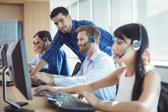 Male supervisor assisting telemarketer at call center. Smiling male supervisor assisting telemarketer at desk in call center Stock Photos