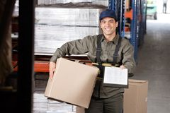 Male Supervisor With Clipboard And Cardboard Box. Portrait of young male supervisor with clipboard and cardboard box at warehouse Royalty Free Stock Image