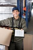 Male Supervisor With Clipboard And Cardboard Box. Portrait of young male supervisor with clipboard and cardboard box at warehouse Stock Image