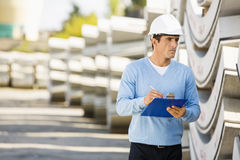 Male supervisor with clipboard inspecting stock at site Stock Image