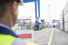 Male supervisor with clipboard in shipping yard Royalty Free Stock Photo