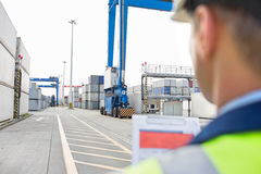 Male supervisor with clipboard in shipping yard Royalty Free Stock Photography
