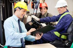 Male Supervisor Communicating With Forklift Driver. Happy male supervisor communicating with forklift driver and foreman at warehouse Royalty Free Stock Images