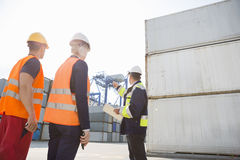 Male supervisor discussing with workers in shipping yard Stock Images