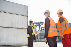 Male supervisor discussing with workers in shipping yard Royalty Free Stock Photos