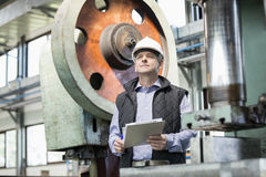 Male supervisor holding clipboard in metal industry.  Stock Images