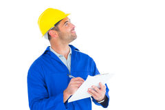 Male supervisor looking up while writing on clipboard. On white background Royalty Free Stock Images