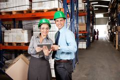 Male Supervisor. Portrait of male supervisor using digital tablet with colleague at warehouse Stock Image