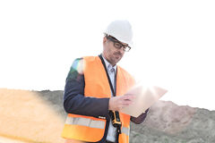 Male supervisor reading clipboard at construction site on sunny day Stock Photos
