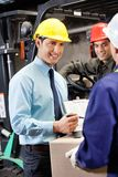 Male Supervisor Showing Clipboard To Foreman. Young male supervisor showing clipboard to mid adult foreman at warehouse Stock Image