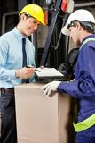 Male Supervisor Showing Clipboard To Foreman. Young male supervisor showing clipboard to mid adult foreman at warehouse Stock Photos