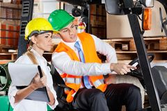 Male Supervisor Showing Something To Colleague At. Male supervisor in forklift showing something to colleague with clipboard at warehouse Stock Photo