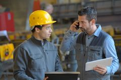 Male supervisor talking on mobile phone with worker at industry royalty free stock photo