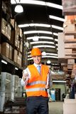 Male Supervisor Using Cell Phone At Warehouse. Portrait of young male supervisor in orange protective vest using cell phone at warehouse Royalty Free Stock Photography