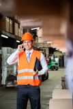 Male Supervisor Using Cell Phone At Warehouse. Young male supervisor in orange protective vest using cell phone at warehouse Royalty Free Stock Photography