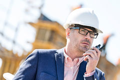 Male supervisor using walkie-talkie at construction site Royalty Free Stock Photo