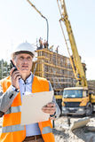 Male supervisor using walkie-talkie while holding clipboard at construction site Stock Photos