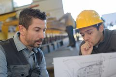 Male supervisor with worker discussing over blueprints in industry royalty free stock photo