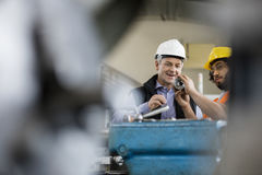 Male supervisor with worker examining metal in industry royalty free stock images