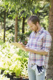 Male supervisor writing on clipboard at plant nursery Royalty Free Stock Images
