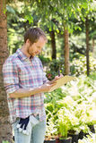 Male supervisor writing on clipboard at plant nursery royalty free stock image