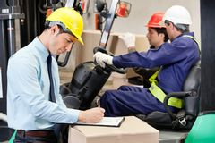 Male Supervisor Writing On Clipboard At Warehouse. Male supervisor writing on clipboard with foremen driving a forklift at warehouse Royalty Free Stock Image