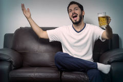 Male supporter watching match on TV. Young bearded man complaining about fault on match. Watching TV at home, alone Stock Images