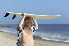 Male surfer carrying surfboard. On beach Royalty Free Stock Photos